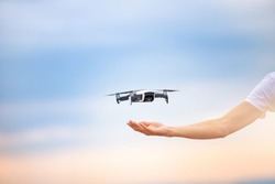 Development of technology, delivery of parcels by drones air. Human hand and quadcopter on sunset background.