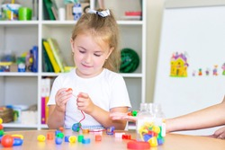 developmental and speech therapy classes with a child girl. Speech therapy exercises and games with beads. The girl has beads in her hands