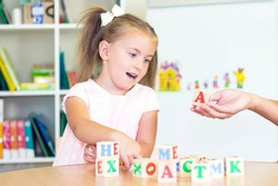 developmental and speech therapy classes with a child girl. Speech therapy exercises and games with letters. dice game