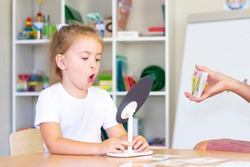 developmental and speech therapy classes with girl. Speech therapy exercises and games with a mirror and cards