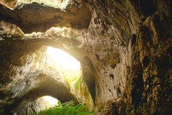 Devetashka cave in Bulgaria - natural attraction. High arches of a huge stone cave with round holes at the top, a tourist road with a fence inside the cave.
