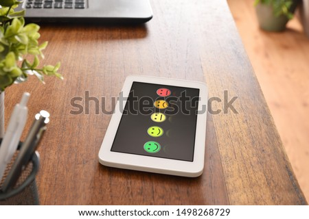Device representing emoticons to assess satisfaction with black screen on the desk of an office. Horizontal composition. Elevated view. #1498268729