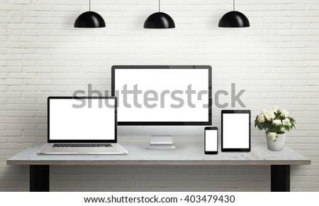 Devices on desk with isolated screen for mockup. Computer display, laptop, tablet and smart phone on office desk. Flowers, lamps and brick wall in background. #403479430