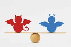 Devil and angel on balance scale - Balance between good and evil