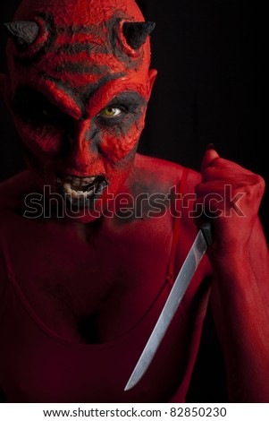 Devil attacking with a knife, black background.