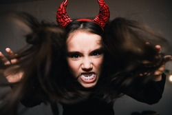 Devil concept on Halloween. Scary thrilling demon girl with long hair, red horns and vampire white teeth on a dark background.