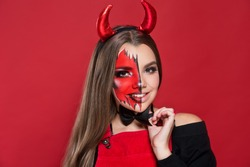Devil. Funny imp with red horns and black bow tie at Halloween party. Halloween makeup. The devil costume.