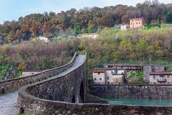 Devil's Bridge over the Sercchio River. Picturesque stone bridge of magnificent architecture. Bridge built a thousand years ago. Cold windy winter day. Travel to fabulous Italy