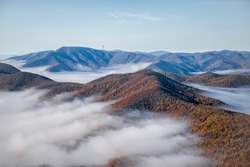 Devil's Knob Overlook at Wintergreen resort town with Blue Ridge parkway road highway in mountains with autumn fall clouds mist fog covering peak high angle view