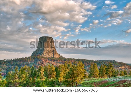Devil's Tower National Monument in Wyoming Under the Early Morning Cloudy Sky with the forest in the foreground ストックフォト ©