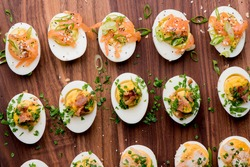 Deviled eggs. Classic American appetizer favorite. Hard boiled eggs, cut in half and white pipped with yolk mixture. Garnished with scallions, salt and pepper. Easter dinner staple.