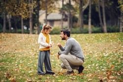 Devilish cute little girl with ponytail standing and looking at her father. Father crouching and reprimanding her. Autumn in park.