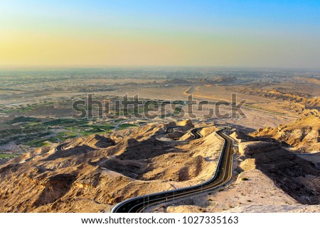 Devious winding road to top of Jebel Hafeet mountain in the outskirts of Al Ain, Abu Dhabi, United Arab Emirates (UAE). Landscape at sunset for background, backdrop.