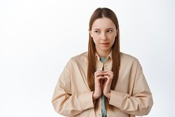 Devious young woman scheming, looking aside at logo with pensive cunning face, steeple fingers, have evil genius plan, thinking, standing over white background