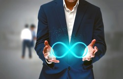 DevOps concept, an IT engineer holding the glowing devops symbol that illustrates the software development practices that combine development and operation teams and automates software processes