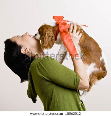 Devoted woman kissing pet dog with bow