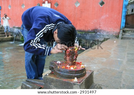 Devotee in Shiva temple is praying to stone lingam. Nepal