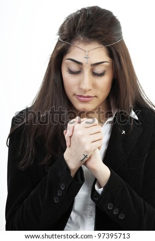 Devout young woman praying with holy cross