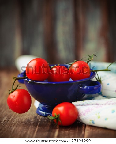 Dewy red tomatoes in blue bowl on the rustic wooden board