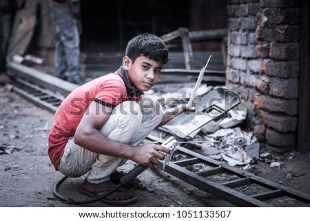 DHAKA, BANGLADESH - MARCH 5, 2018: A young boy is doing child labor in a metal workshop where is he welding a metal ladder