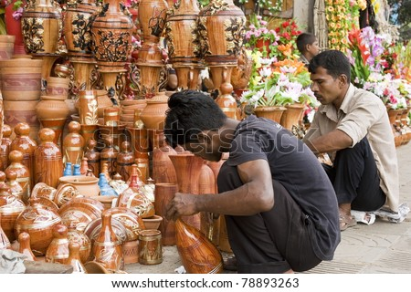 DHAKA, BANGLADESH – SEPTEMBER 21: Two unidentified men paint clay-made pottery in a roadside shop on September 21, 2010 in Dhaka, Bangladesh. Shops like this sell handcrafts to tourists and locals.