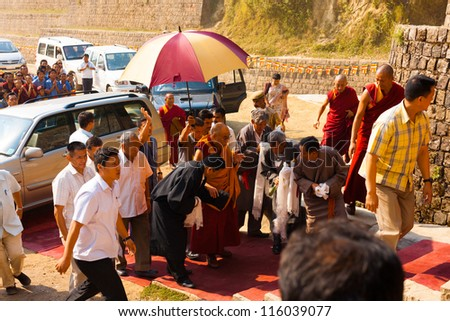 Dharamsala, India - June 25, 2009: A phalanx of men surrounds his Holiness, the Dalai Lama receiving special attention on his way on the red carpet to give a speech