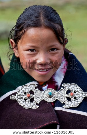 DHO TARAP, NEPAL - SEPTEMBER 11: Tibetan girl Pema Sangku, 9, from the village of refugees poses for the photo during the Dho Tarap Full Moon Festival on September 11, 2011 in Dolpo, Nepal