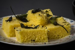 Dhokla is spongy food eatable as snacks in India, the main focus is in center of image bringing the close up view.