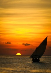 Dhow sailing during sunset in Zanzibar. Dhow is a wooden vessel with a sail, used to transport goods. Mostly used in Indian ocean.