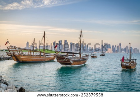 Dhows moored off Museum Park in central Doha, Qatar, Arabia, with some of the buildings from the city\'s commercial port in the background.
