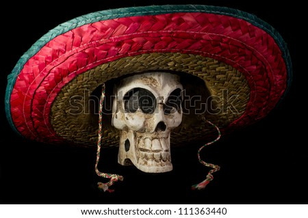 Dia De Los Muertos (Day of the Dead) skull wearing colorful Mexican sombrero on isolated on black background