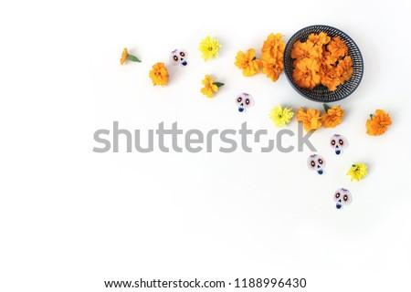 Dia de los Muertos, Mexican Day of the Dead desk composition. Orange tagetes, marigold, chrysanthemum flowers and decorative paper skull stickers. White table background. Halloween flat lay, top view - Shutterstock ID 1188996430