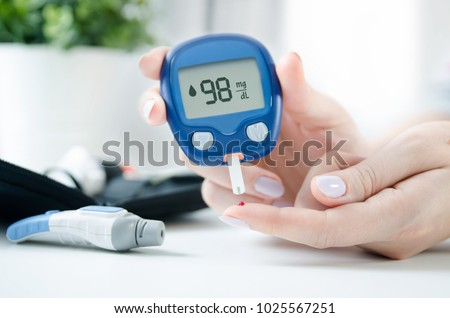 Diabetes checking blood sugar level. Woman using lancelet and glucometer at home. #1025567251