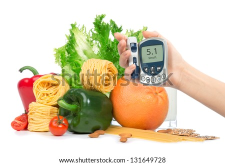 Diabetes concept glucose meter in hand and healthy organic green and red pepper, tomatoes, almonds, fresh salad, spaghetti, grapefruit, glass of milk on a white background