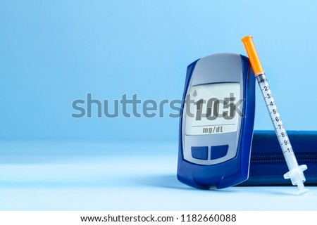 Diabetes. Diabetes concept. Glucose meter and injections for insulin on a blue background. Diabetic supplies. Copy space