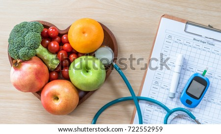 Diabetes monitor, Cholesterol diet and healthy food eating nutrition, World diabetes day concept with clean fruits in nutritionist's heart dish and patient's blood sugar control, diabetic measurement