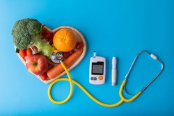 Diabetes monitor, diabetic measurement. World diabetes day concept with clean fruits in nutritionist's heart dish.