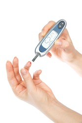 Diabetes patient measuring glucose level blood test using mini glucometer and small drop of blood from finger test strips isolated on a white background