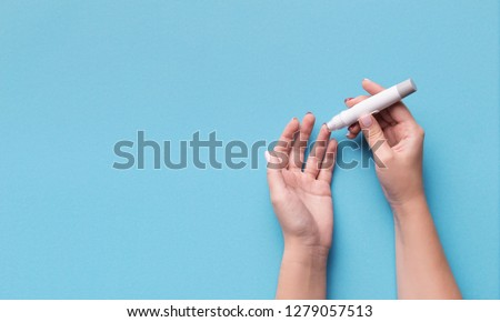 Diabetes test. Woman hands checking blood sugar level by Glucose meter on blue background, copy space