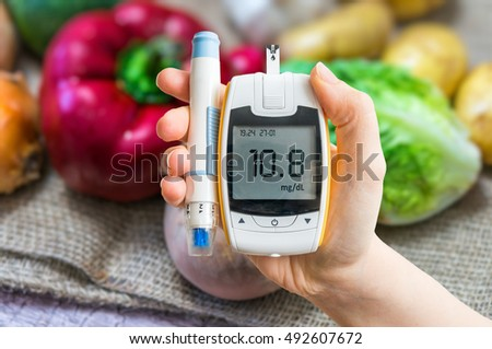 Diabetic diet and diabetes concept. Hand holds glucometer. Vegetables in background. Stock photo ©