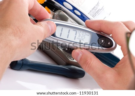 Diabetic is doing a diabetes glucose level finger blood test. In background there are older, bigger devices. Modern, mini monitor in her hands.