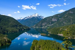 Diablo Lake in the North Cascades of Washington State under a blue sky with a perfect reflection of  Davis Peak mountain in the fresh water during Spring.  This lake supports a hydroelectric project.