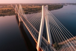 Diagonal aerial view of a white suspension bridge with three huge pillars above a river leading to a straight highway at sunrise in a rural area
