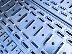 Diagonal arrays of holes and slits in galvanized perforated cable trays - abstract image. Metal digital infrastructure concept. Close up image.