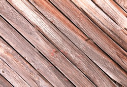 diagonal slanted barn wall siding boards weathered faded and worn as an interior or exterior design architectural scene