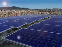 Diagonal view of solar panels on a rooftop with a view city skyline on a sunny day with a blue sky and solar glare effects.