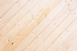 Diagonal wooden lining background. Bleached wooden texture. New wooden boards on wall. Close-up. Striped background of diagonal narrow wooden boards without varnish.