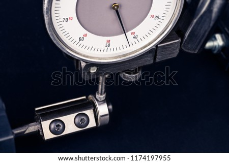 Dial gauge when measuring endmill with ball bearing. Close-up of measurement by probe indicator in metal holder. End mill with steel tipped tool on black background. Quality control in engineering. ストックフォト ©