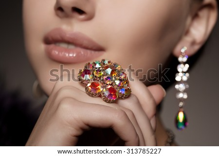 Diamond. Brilliant. Antique old vintage earrings and ring. Jewelry on her finger at the girl close-up on a  #313785227