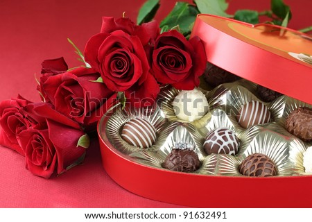 Diamond engagement inside of a heart shaped box of chocolate truffles with red roses. Selective focus on diamond ring with soft blurred background.